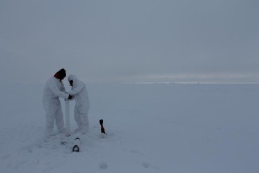 Dr. Anna Aguilar-Islas and Dr. Rob Rember from the University of Alaska, Fairbanks wear Tyvek suits and special gloves to collect ice cores that will be analyzed for contamination-prone metals.